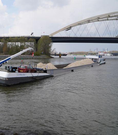 Binnenvaartschip loopt vast op zandbank bij Van Brienenoordbrug en moet wachten op hoog water