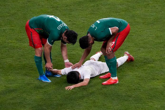 De Mexicaanse voetballers Jesus Angulo en Luis Romo troosten Japanner Takefusa Kubo na de troostfinale in het voetbaltoernooi.