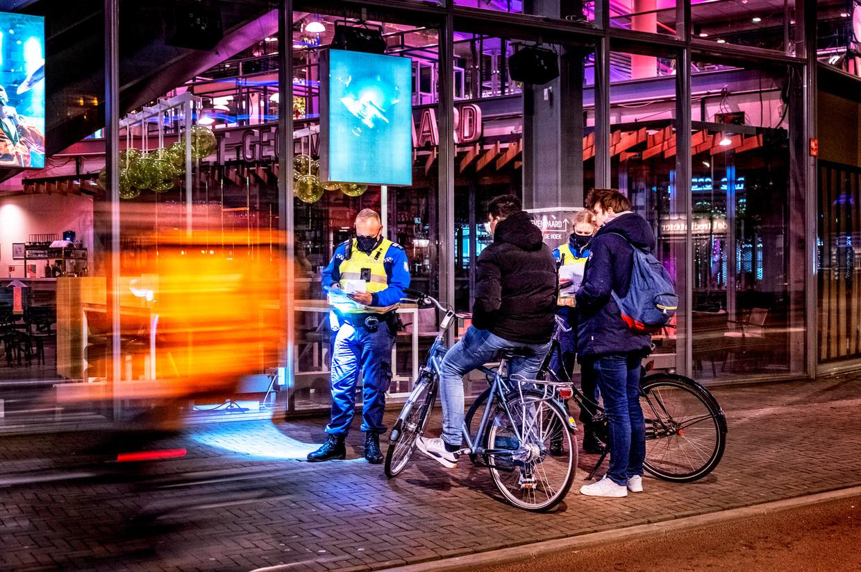 Handhavers Marco en Evita controleren de werkgeversverklaring van twee jongens bij concertpodium TivoliVredenburg. Beeld Raymond Rutting / de Volkskrant