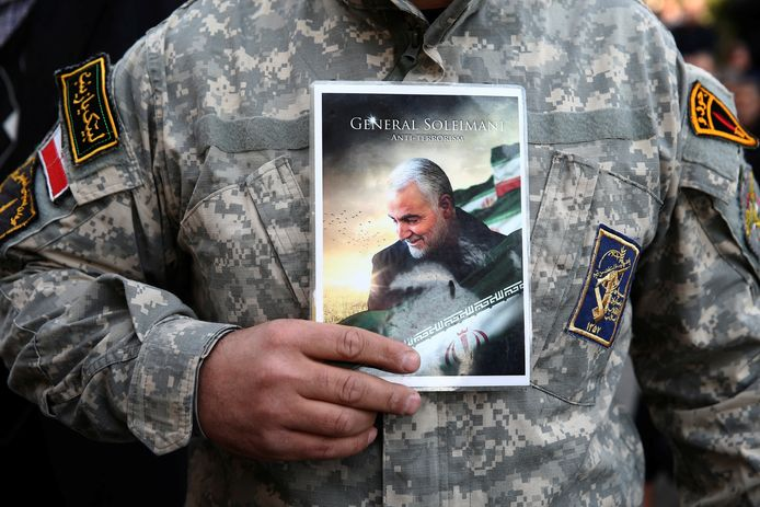Een demonstrerende soldaat houdt een foto van Soleimani voor de borst.