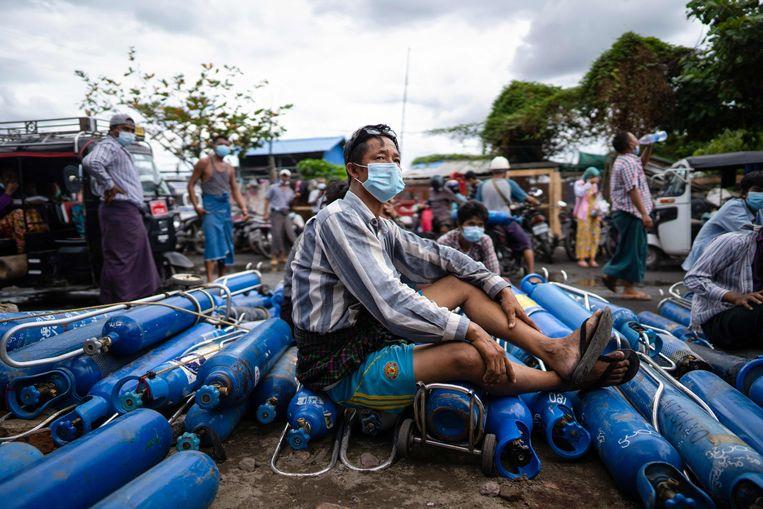 Een man wacht bij een fabriek in de Myanmarese stad Mandalay tot hij zijn zuurstofflessen kan laten vullen.  Beeld AFP