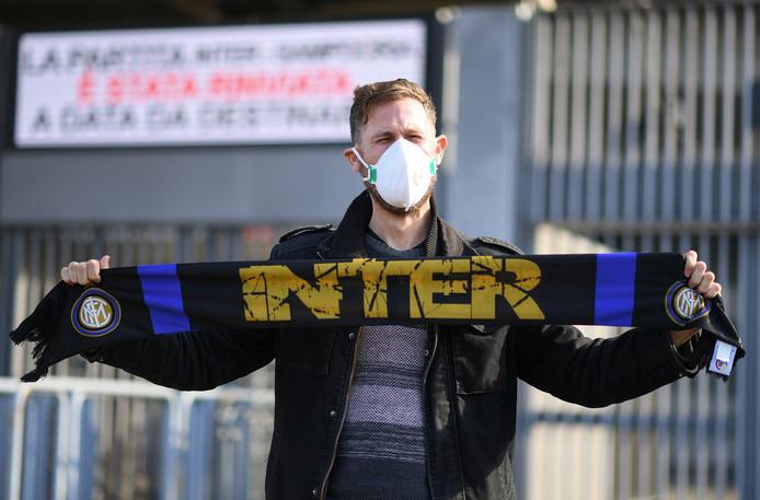 Een Inter-fan draagt een mondkapje voor het coronavirus.