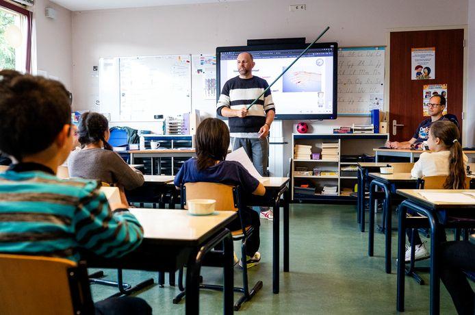 Een leraar laat met een stok aan basisschoolleerlingen zien wat 1,5 meter is