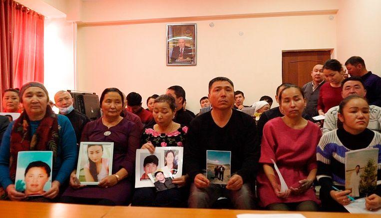 Familieleden van vermiste Kazachen uit Xinjiang houden de foto's van hun geliefden omhoog. Beeld AP