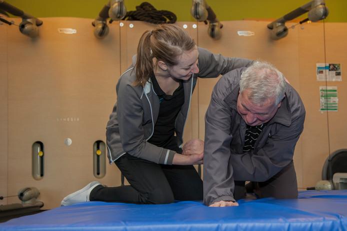 Bij de training van Vallen VerledenTijd bij FysioZwolle leren ouderen op een dikke mat hoe ze door kunnen rollen na een valpartij.