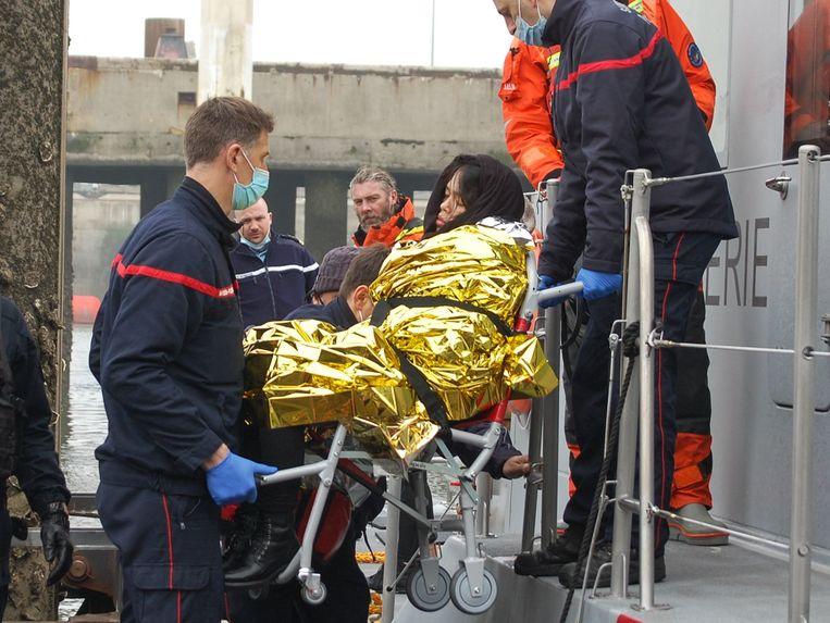 Een zwangere Vietnamese vrouw wordt in Calais van een schip van de Franse kustwacht getild, nadat het sloepje waarop ze het Verenigd Koninkrijk probeerde te bereiken in moeilijkheden was gekomen. Ongeveer zestig migranten werden bij deze operatie gered.  Beeld AFP