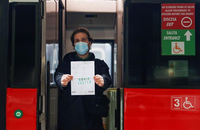 Een passagier laat een negatieve testuitslag zien op de intercitytrein die tussen Rome en Milaan rijdt.