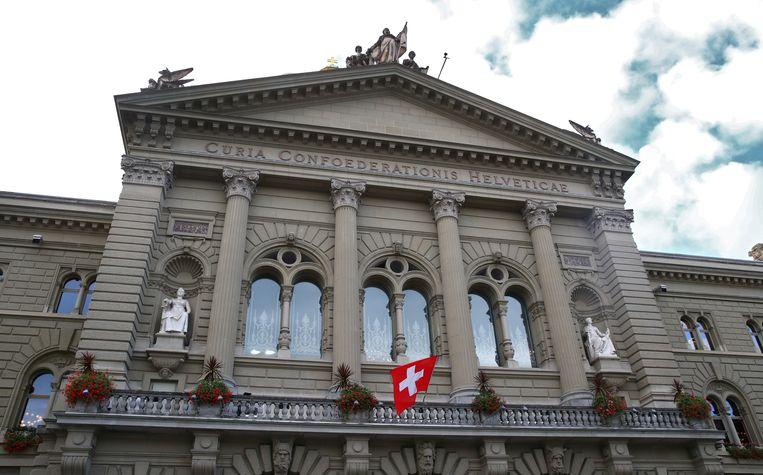 De Zwitserse vlag hangt uit bij het parlementsgebouw in Bern. Beeld REUTERS