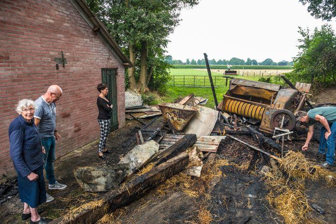 Hettie Wolfsen inventariseert de schade van de verbrande schuur met dochter Rita, zoon Jacob (l) en schoonzoon Jan (r).