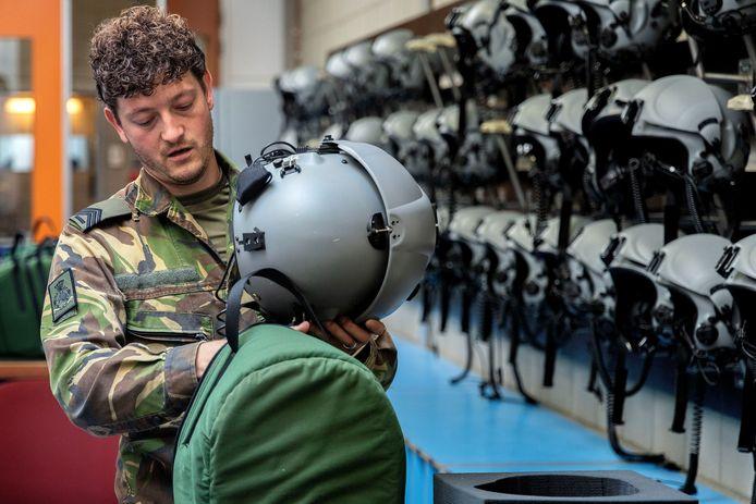 Op de afdeling vlieguitrustingtechniek laat Thijs een wand met helmen zien, gerangschikt op piloot.