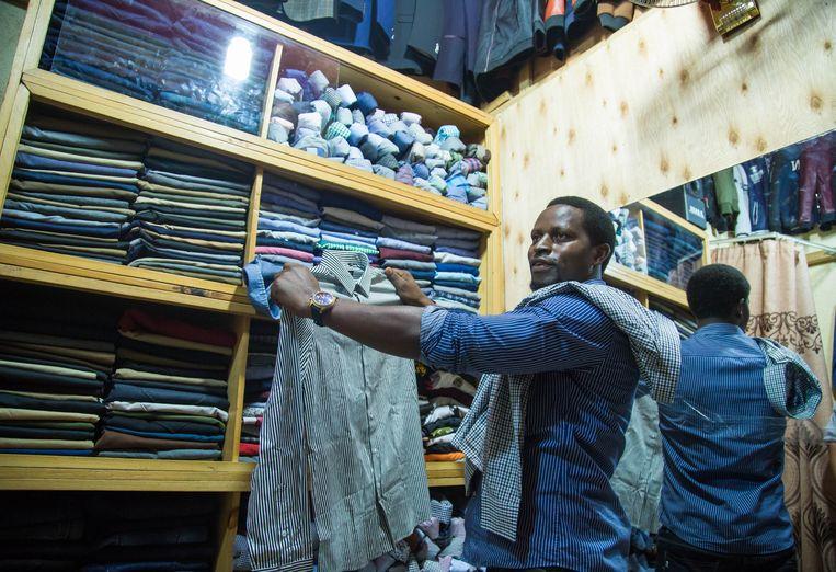 Een kledingverkoper toont een tweedehands overhemd in Kigali, de hoofdstad van Rwanda. Omdat de invoer van gebruikte kleren duurder is gemaakt, is hij ook goedkope eerstehands kleding uit China gaan verkopen. Beeld Nadège Karemera