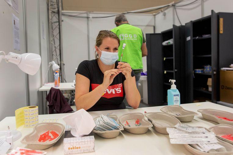 Lois Goedhart (24) is aan het werk in de sporthal in Uitgeest, waar de GGD een priklocatie heeft ingericht.  Beeld Maartje Geels