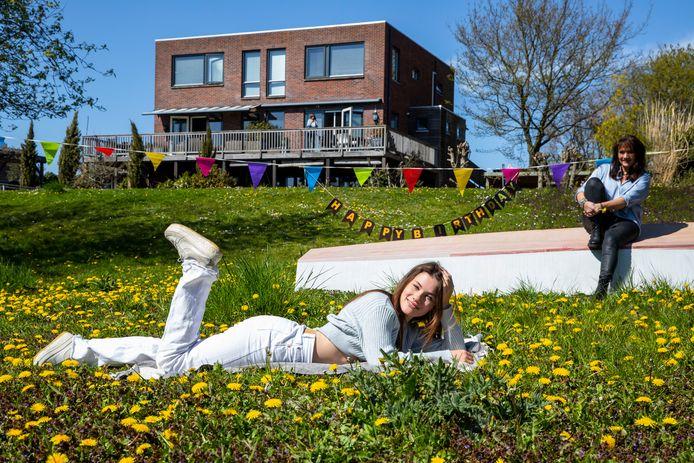 Fenne Smits in haar tuin met haar moeder Katja. In de achtergrond hangen de vlaggetjes voor haar verjaardag nog.