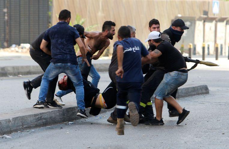 Een gewonde bij gevechten in Beiroet wordt afgevoerd. Bewoners vrezen dat de schermutselingen uitmonden in een nieuwe burgeroorlog. Beeld Reuters