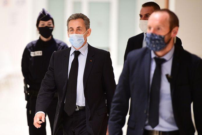 Nicolas Sarkozy (midden) bij aankomst bij de rechtbank in Parijs.