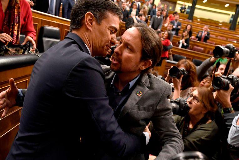 Sanchez (links) krijgt na de stemming felicitaties van Pablo Iglesias van het uiterst linkse Unidas Podemos. Beeld AFP