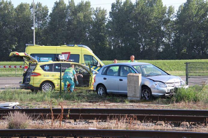 De auto reed door het hek langs de spoorlijn.