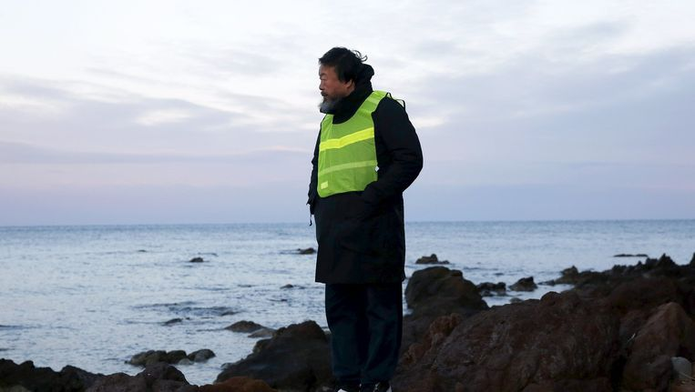 Chinees kunstenaar Ai Weiwei kijkt uit over de Middellandse Zee vanaf een strand op het Griekse eiland Lesbos, waar nog steeds nieuwe vluchtelingen aankomen. Beeld reuters