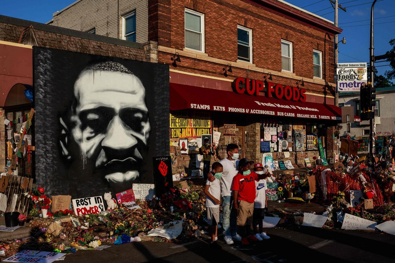 Een vader en kinderen poseren bij een herdenkingsplaats voor George Floyd, vlakbij de plek waar hij overleed in de stad Minneapolis.