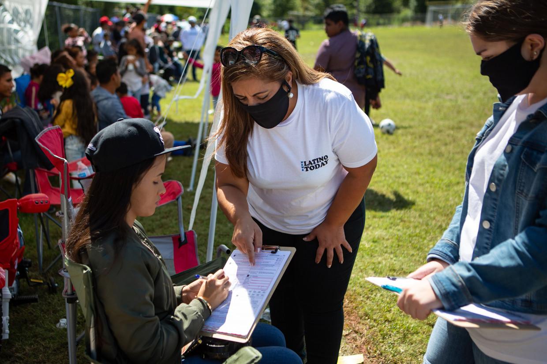 Een vrouw gaat rond met biljetten om kiezers te registreren tijdens de pauze van een sportwedstrijd. De opkomst bij latino's is gewoonlijk laag. Beeld Photo News