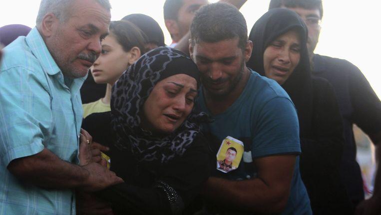 Familieleden huilen op de begrafenis van een Koerdische strijder die is gesneuveld tijdens gevechten met ISIS. Beeld reuters