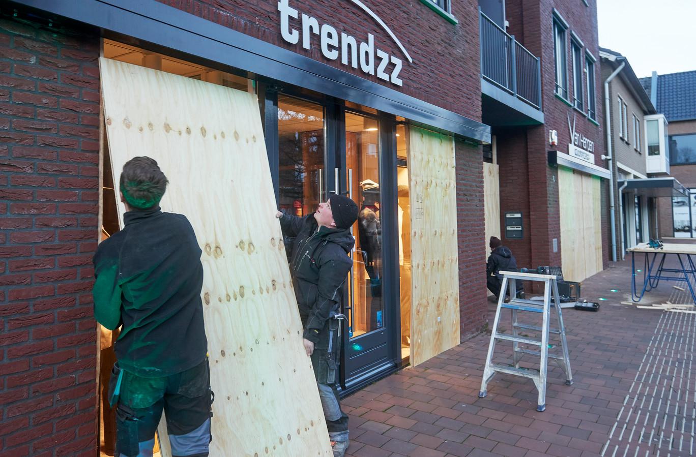 Medewerkers van Verstegen Bouw en Timmerwerk zijn bezig met het dichttimmeren van de winkel van Trendzz in Heesch. Dit uit voorzorg voor de gevreesde rellen.
