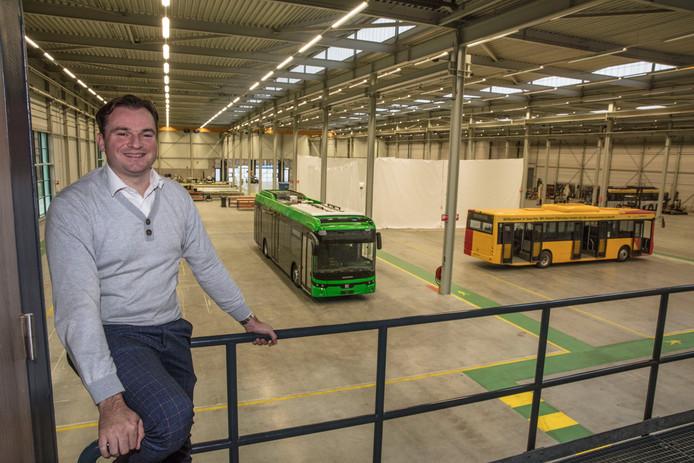 Directeur Peter Bijvelds van Ebusco in Deurne, met op de achtergrond een in groen uitgevoerde Ebusco 2.2.
