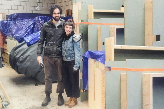 Thijs en Ella bij de prefab onderdelen van hun tiny house. Ze staan nu nog in de opslag, maar dit najaar bouwen ze er hun houten huisje mee in Pendrecht.