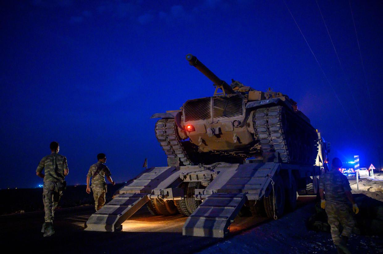 Een tank van het Turkse leger wordt dinsdag van een oplegger gereden in de buurt van de grens met Syrië.   Beeld Foto AFP