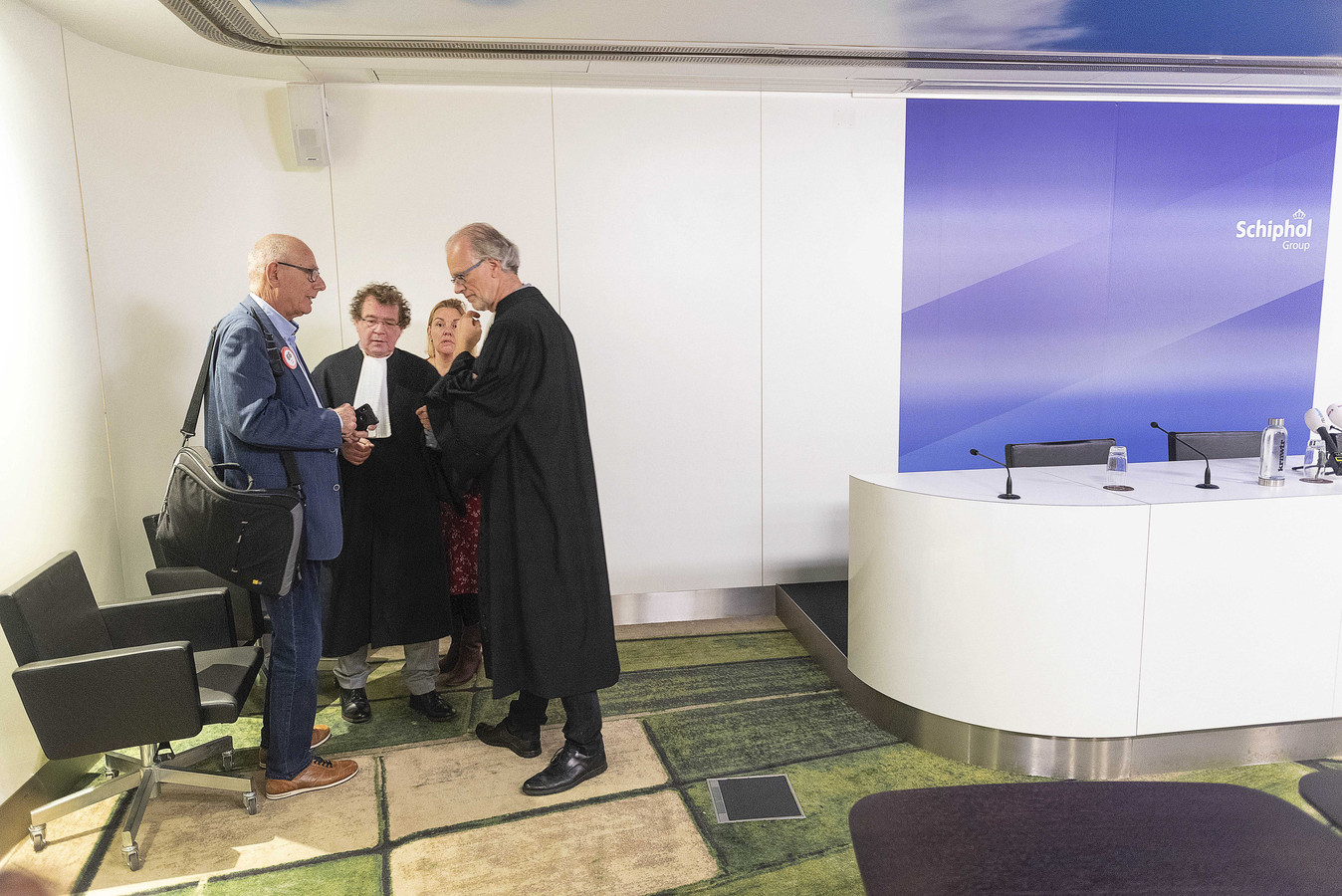 De advocaten van de vakbonden overleggen voorafgaand aan het kort geding van Schiphol tegen de vakbonden.