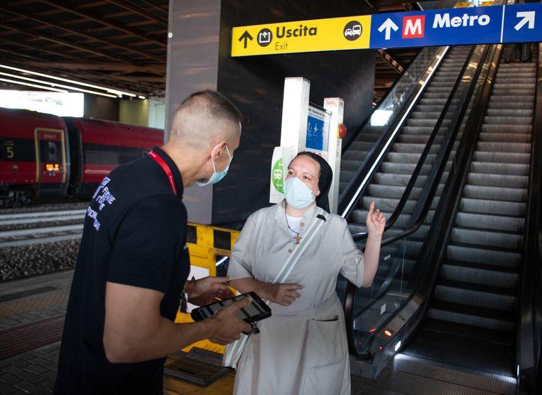 Een reiziger moet haar green pass laten zien op een station in Rome.  Beeld EPA