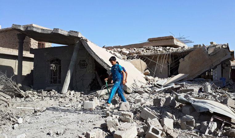 Iraakse jongens lopen langs huizen die zijn getroffen door een luchtaanval van het leger. Beeld epa