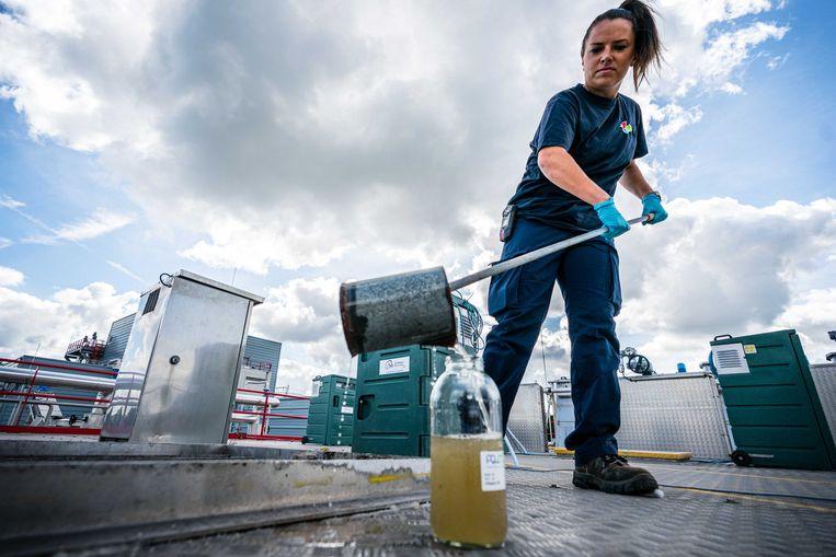 Een medewerker van de rioolwaterzuivering neemt een monster van het rioolwater. Het water wordt onderzocht op onder meer virusdeeltjes om zodoende te kunnen vaststellen hoeveel mensen het coronavirus onder de leden hebben en kunnen overdragen.  Beeld ANP