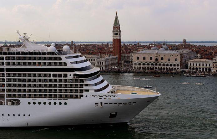 Sleepboten begeleiden cruiseschip MSC Orchestra bij zijn vertrek uit Venetië op 5 juni 2021. Het cruiseschip was twee dagen eerder het eerste dat na zeventien maanden weer afmeerde in de Dogenstad.