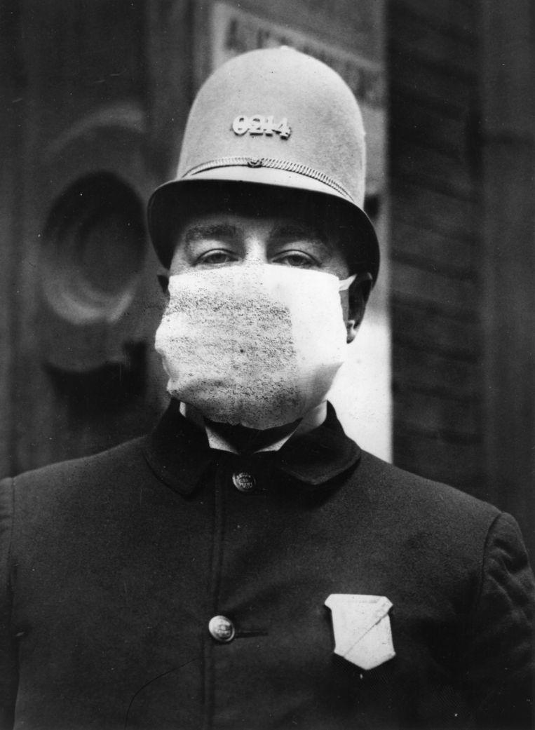 Een Amerikaanse politieagent met een 'griepmasker' in 1918.  Beeld Getty Images