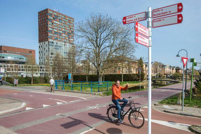 Martin Haaring van de gemeente Zoetermeer fietst langs de bordjes van het Fietsnetwerk Zoetermeer dat hij hielp vernieuwen.