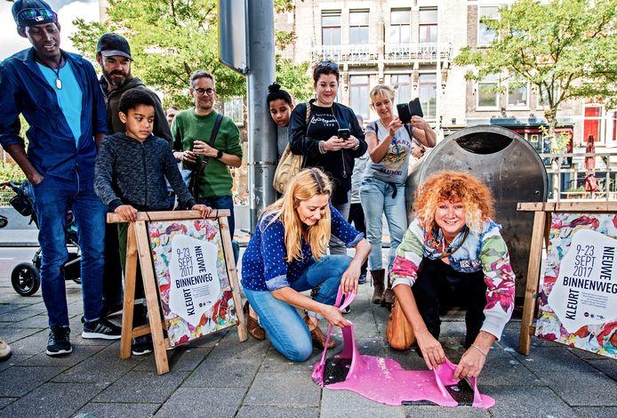 Erica Sonneveld en Carrie Jansen 'onthullen' de tegels die herinneren aan het kauwgomkunstproject.