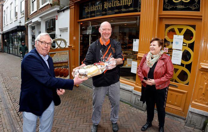 Wethouder Sjef Evers overhandigt Koos Holtkamp een afscheidscadeau, terwijl zijn vrouw Kiek toekijkt.