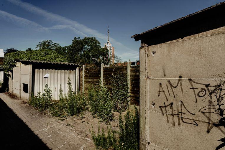 'Aim for the stars' staat op een garageboxen die wordt gebruikt slaapplaats, met zicht op de sociale woonblok Sint-Maartensdal. Beeld Eric de Mildt
