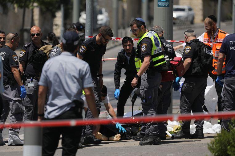 Israëlische veiligheidsagenten bij het lichaam van de gedode Palestijn die maandag twee Israëliërs had neergestoken bij het hoofdbureau van de politie in Jeruzalem.   Beeld EPA