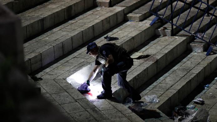 Een politieagent doet onderzoek in Jeruzalem na een aanval die werd opgeëist door IS.