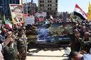 Aanhangers van het Assad-regime dragen Syrische vlaggen en portretten van hun president tijdens een betoging in Aleppo uit protest tegen de westerse aanval.