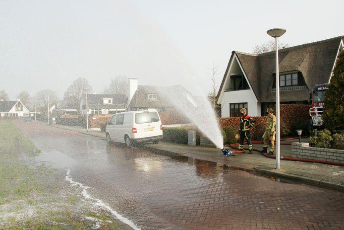 De brandweer heeft het waterkanon nodig om een kelder aan de Pastoor Reintjesstraat in Hellendoorn leeg te pompen.