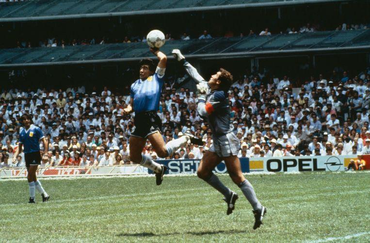 Diego Maradona en doelman Peter Shilton springen naar de bal. De Argentijn gebruikt zijn hand, maar het doelpunt wordt goedgekeurd.  Beeld Bob Thomas / Getty