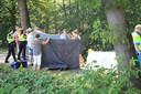 Omstanders helpen doeken omhoog te houden voor de slachtoffers in De Rips