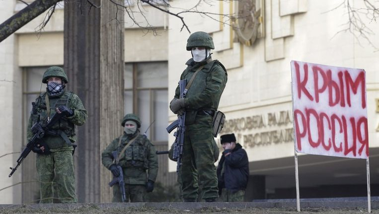 Mannen in legeruniform in Simferopol, bij het parlementsgebouw van de Krim. Beeld epa