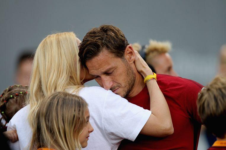 AS Roma-middenvelder Francesco Totti zoekt troost bij zijn vrouw Ilary Blasi na zijn allerlaatste wedstrijd in zijn carrière. Beeld Getty Images