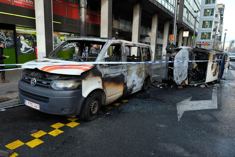 Een politiewagen die in brand werd gestoken door relstokers