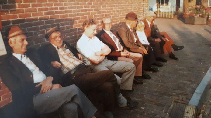 De Burghse klapbank in 1984, toen nog zonder afdakje, aan de zijmuur van de voormalige slagerij aan de Ring. Met (vlnr) Krijn Schoonaard, Jacob de Meij, Jaap de Koning, Daan van der Wekken, dhr Semeijn en Co van der Have. De naam van het meisje en de man in oranje broek is onbekend.