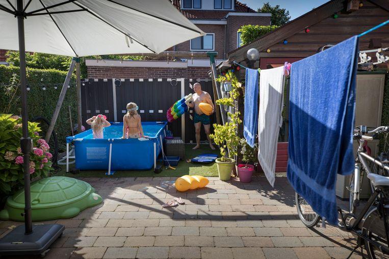 Na een lange werkdag plonst Ronald Helder uit Muiden in zijn zwembad,  waar dochters Fenna (6) en Emily (9) hem wild spetterend verwelkomen. Beeld Werry Crone